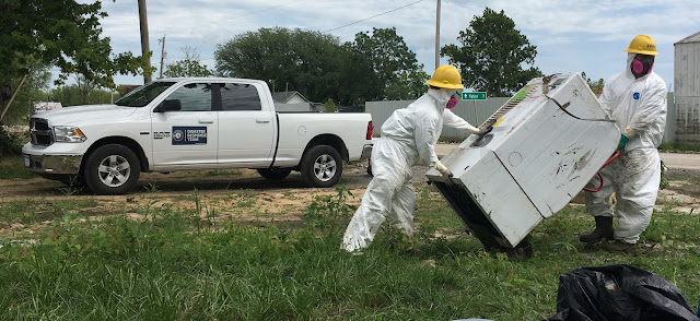 Two AmeriCorps members carry a water-damaged dryer across a lawn. They are wearing white Tyvek protectives suits and yellow hard hats.