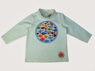 e924bca3d Esta camiseta de niño de color crudo tiene el cuello chimenea y está  personalizada con el nombre del niño bordado en azul marino.