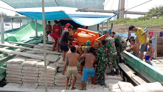 Dalam Pelaksanaan Serpas TMMD 110 Anggota Kodim 0912/Kutai Barat Membawa Perlengkapan dan Bahan Material Lewat Jalur Sungai Mahakam