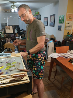 Mike at his easal wearing a pair of hand sewn shorts. The shorts have cartoon figures of sea creatures on them.