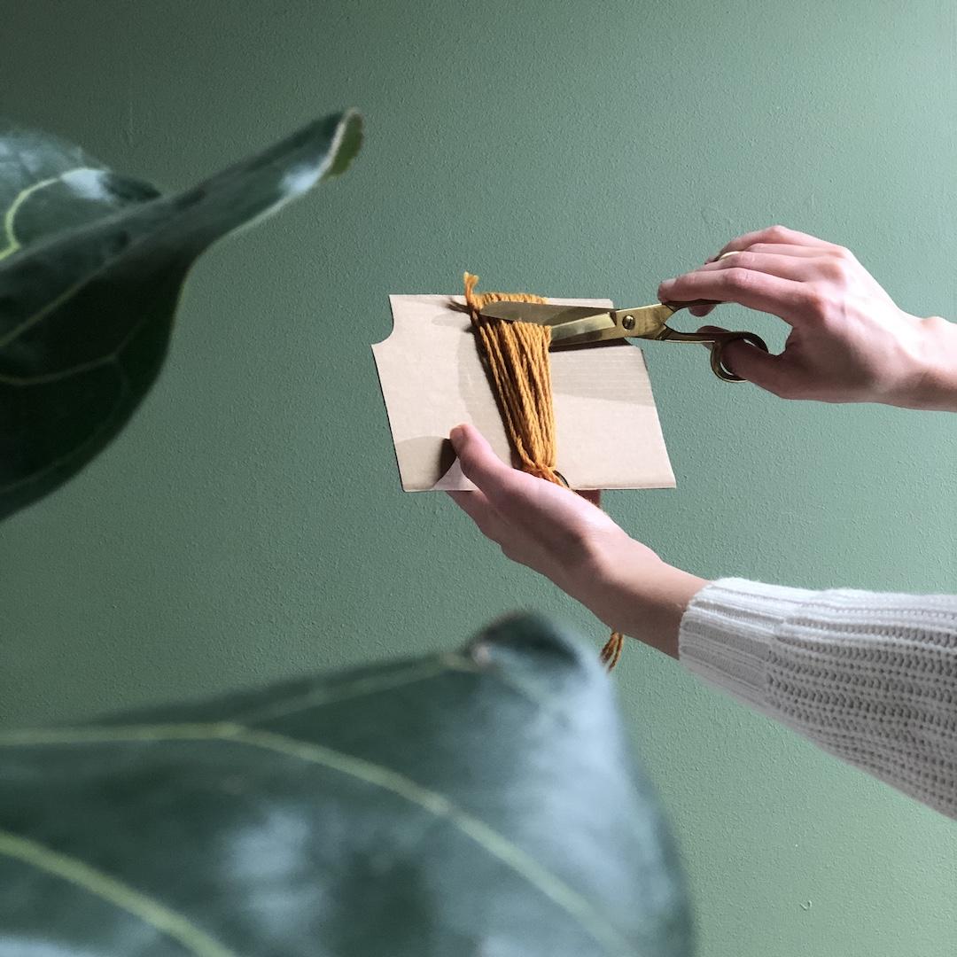 Nainen leikkaa pahvin ympärille puoliteltuja villalankoja kahtia.