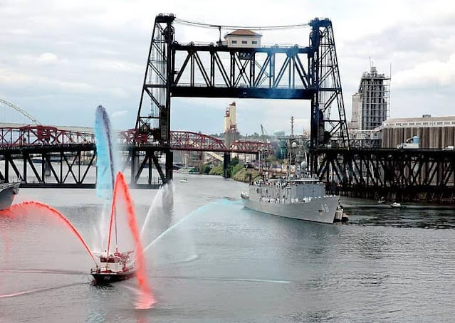 A fireboat gives a water salute to the USS Vandegrift by the Steel Bridge in Portland, Oregon.