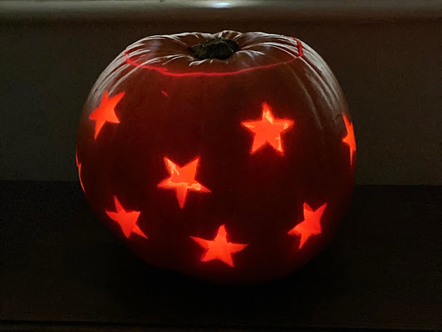a lit up pumpkin in a dark room with star shapes all over it