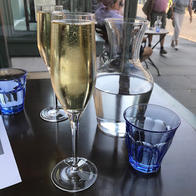 Two glasses of prosecco and two of water on a dark brown wooden table