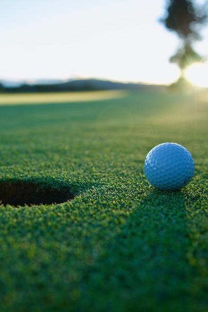 The sunrise shines on a golf hole with a golf ball