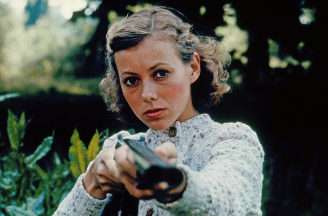 Jenny Agutter pointing a shotgun