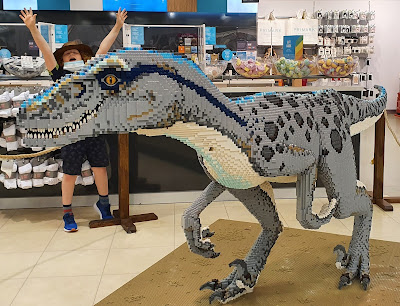 Blackburn Brick Trail Velociraptor in Primark with young boy leaping and waving in background