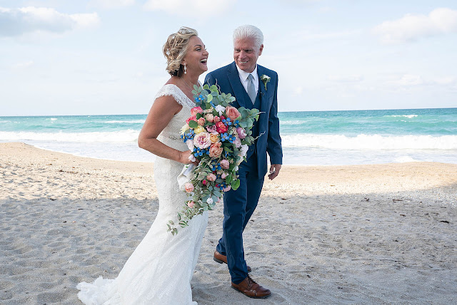 Bride and Groom holding hands and walking on the sand