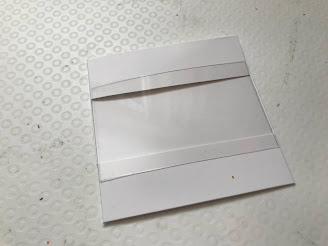 A piece of acetate laying of the top of a white square card front that has a middle section cut out of it