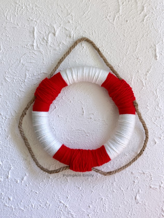A red and white wreath made with yarn and nautical rope.