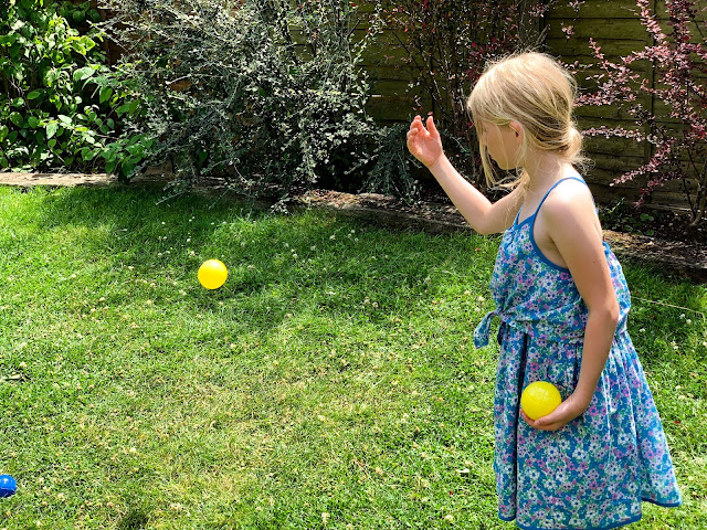 7 year old throwing yellow plastic boules balls
