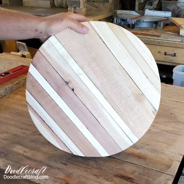 After gluing rows of reclaimed wood boards together, it's time to cut them into a circle. Begin by notching off the corners with the table saw. Then work your way around the board, shaving off little pieces as you go until you have a circle.  Use the grinder to sand down the edges when finished. Watch the sped up video of the process that took about 5 minutes.