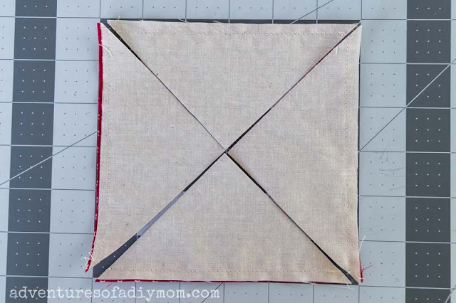 image depicting cuts through fabric diagonally from corner to corner in both directions