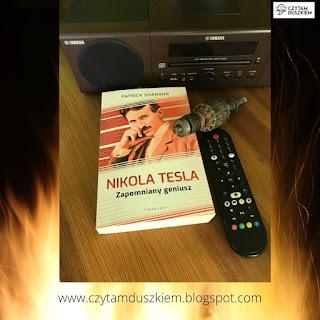 """Książka pt. """"Nikola Tesla. Zapomniany geniusz"""" leży przez radiem, a obok część silnika oraz pilot do telewizora."""
