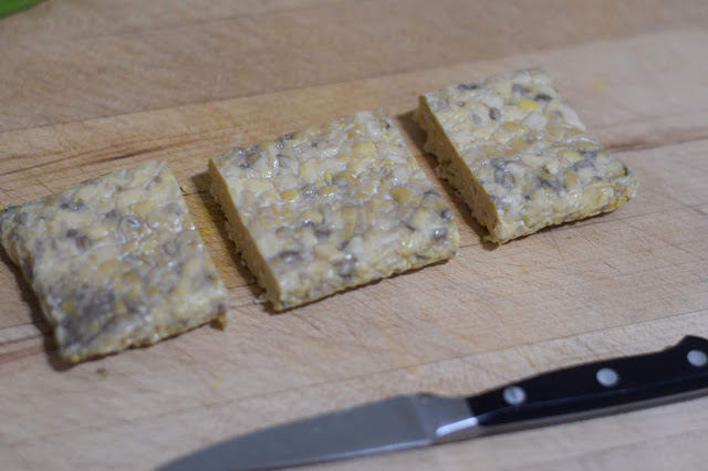 A block of tempeh cut into three parts.
