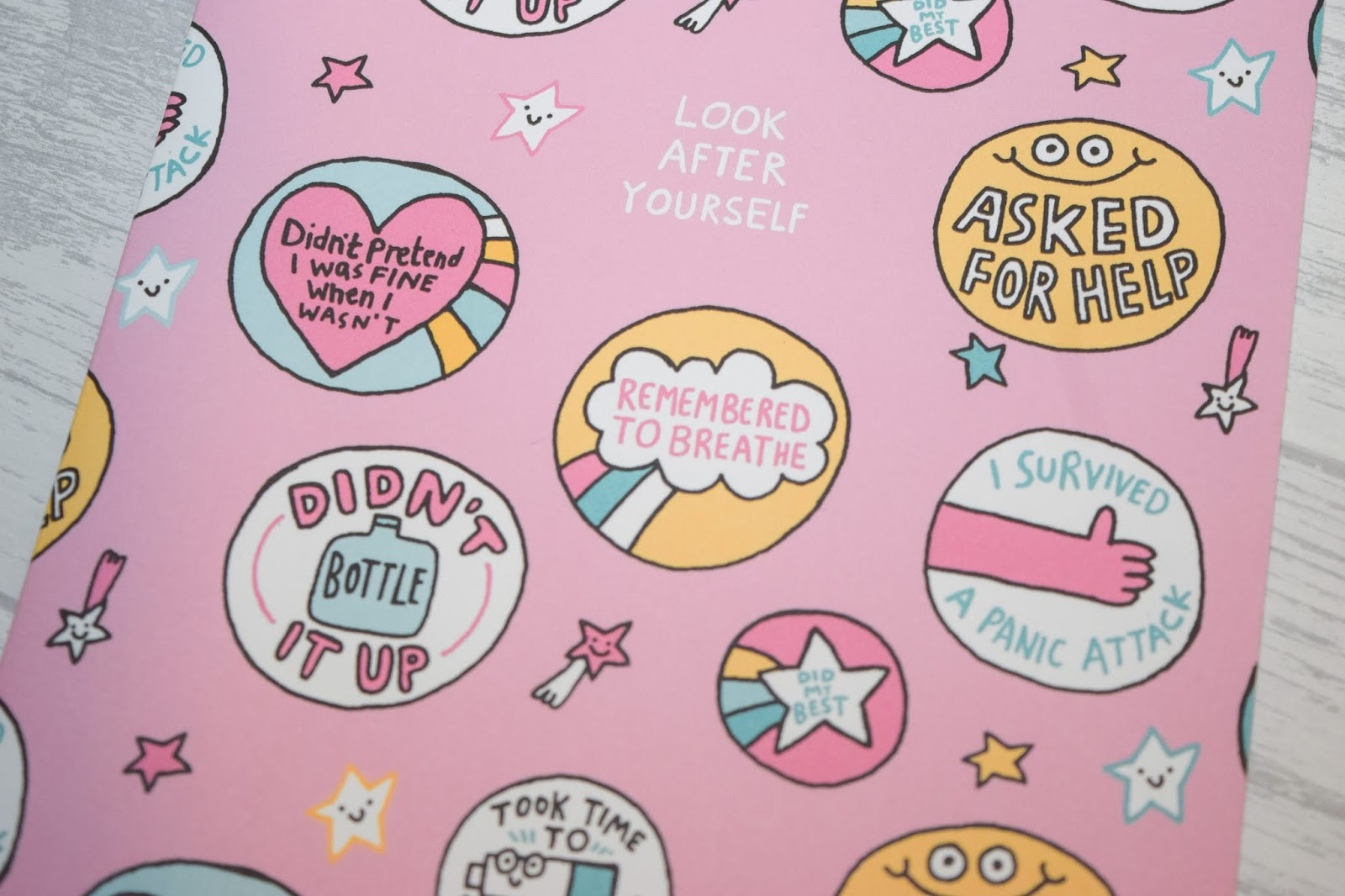 A close up of a pink notebook with round circles filled with motivational phrases.