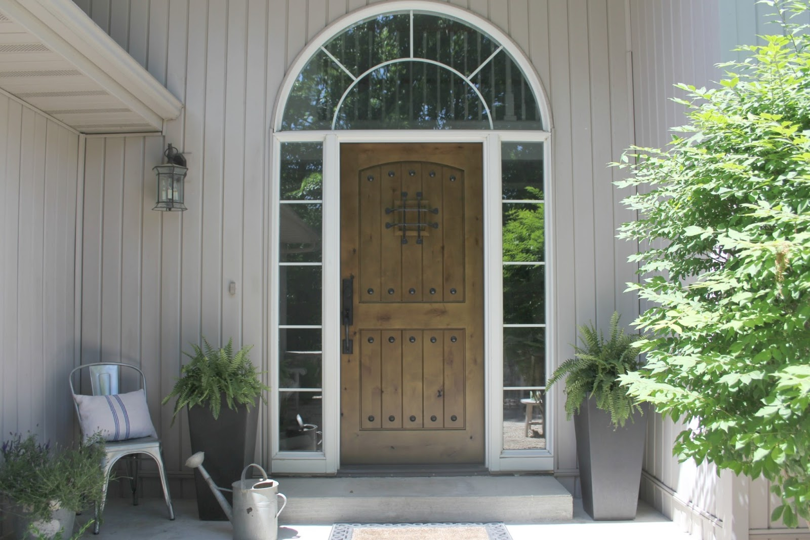 Knotty alder front door (Pacific Entries) and country courtyard by Hello Lovely Studio