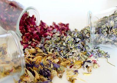 Desodorante de ambiente natural casero. Tres recipientes de vidrio volcados sobre una superficie blanca, con pétalos de flores secas saliendo de su interior.