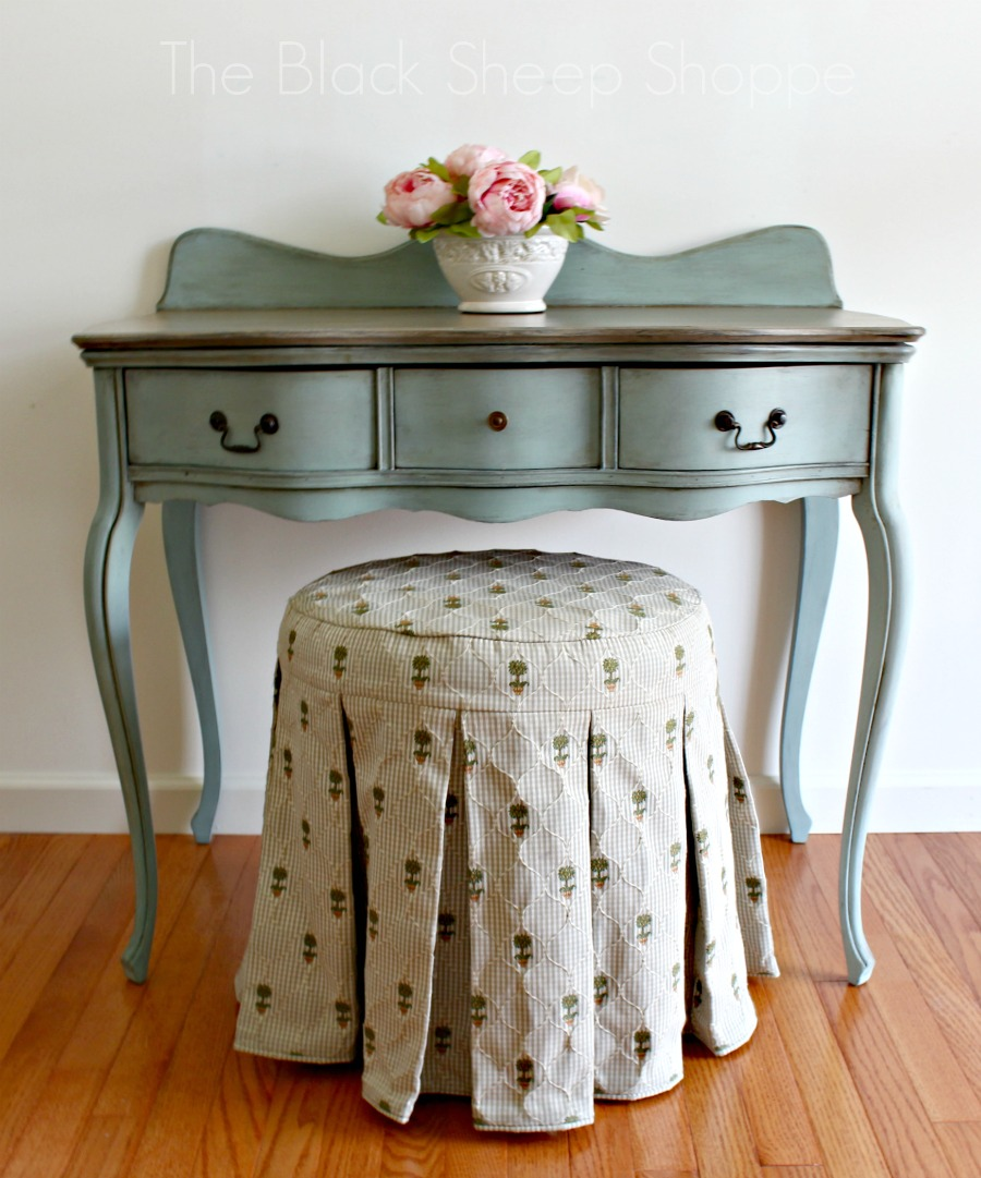 Desk paired with upholstered vanity stool