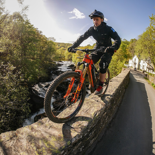 Tom Cardy rides a wall parapet over a river.