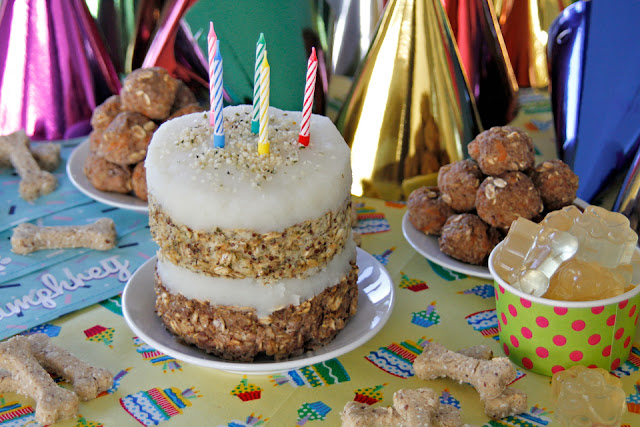 Dog birthday party buffet table with layered birthday meatloaf cake and homemade dog treats.