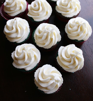 swirls of cream cheese frosting piped onto cupcakes