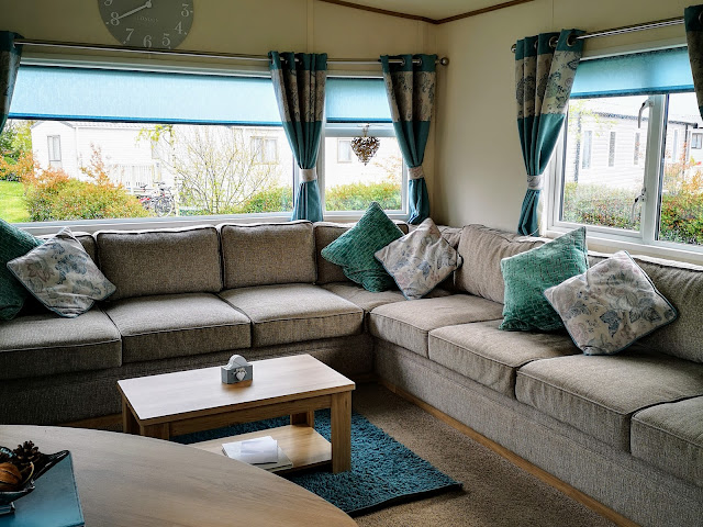 The inside view of our accommodation at Tattershall Lakes. Living Room of an 8 berth caravan with cream fabric corner sofa and turquoise accessories.
