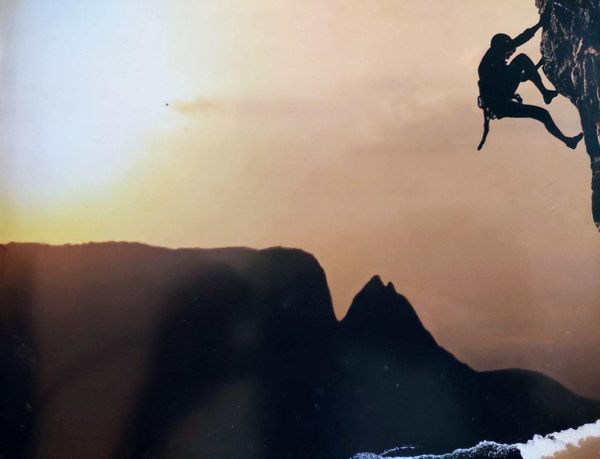 Image contains a man climbing on a rock
