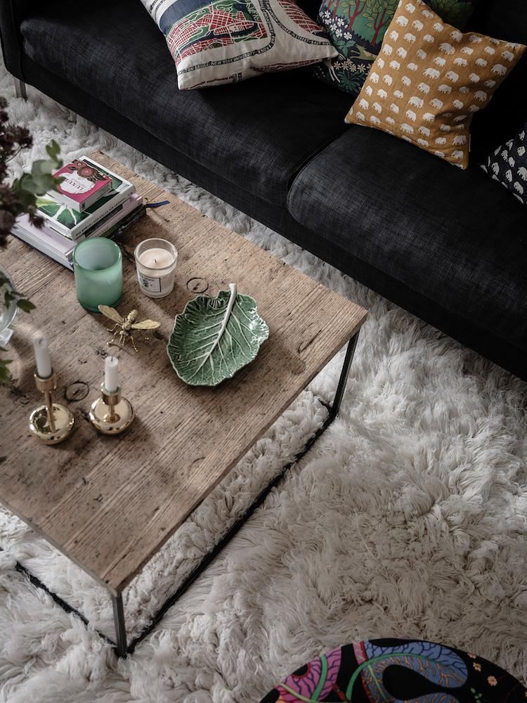 Sofá negro, mesa de madera reciclada y alfombra peluda en un piso nórdico