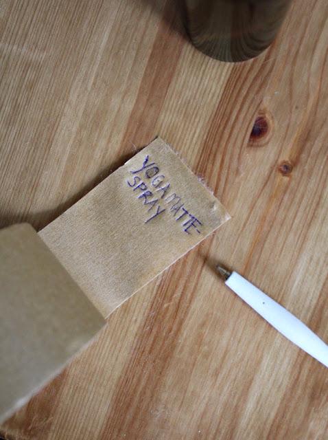 Bruker papirteip til å lage en etikette på sprayen