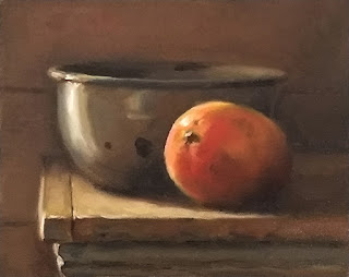 Oil painting of a mango beside an enamelware bowl on a bench top.