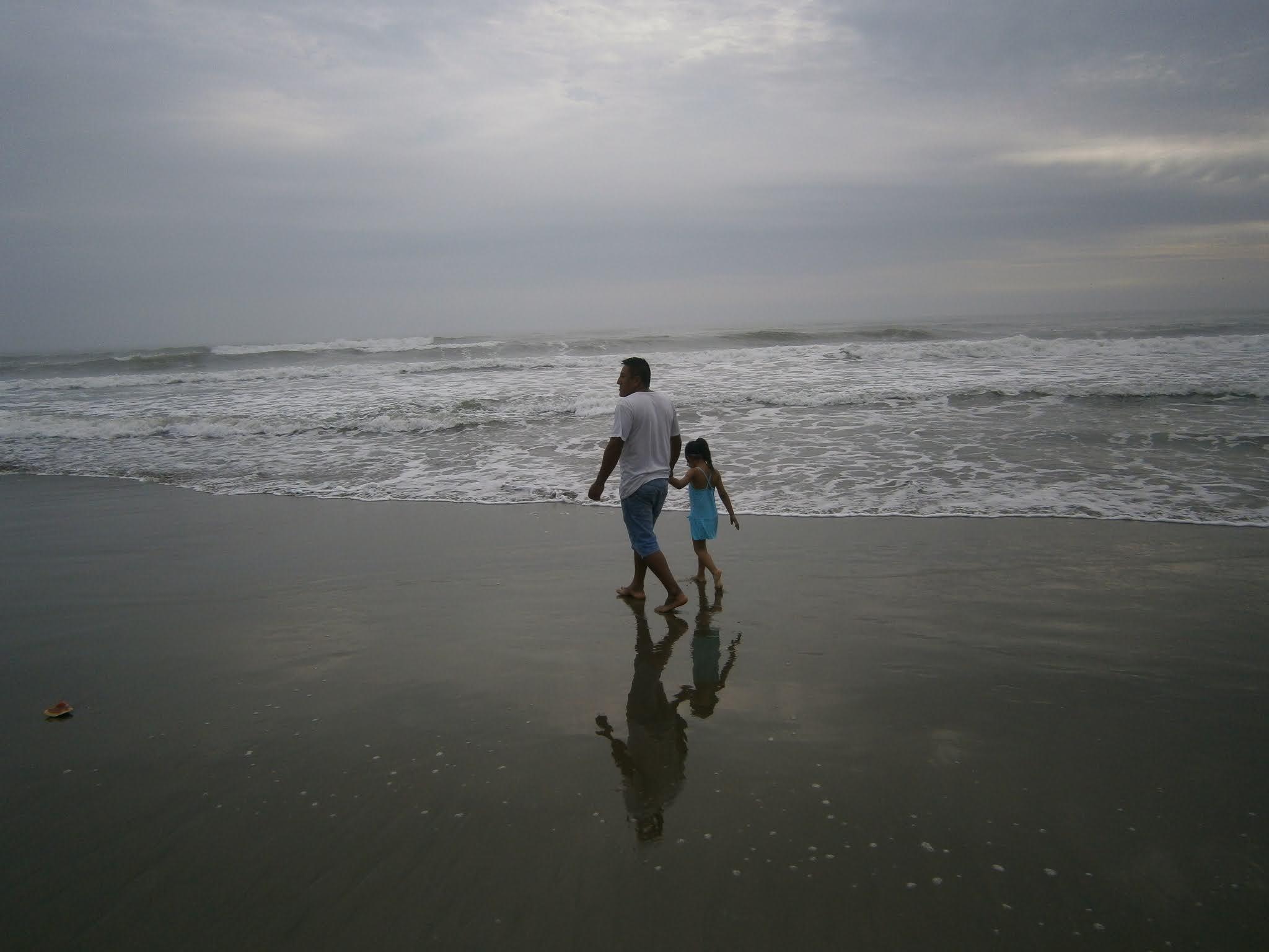 fotografía de Personas adultas y niños caminando por la Playa