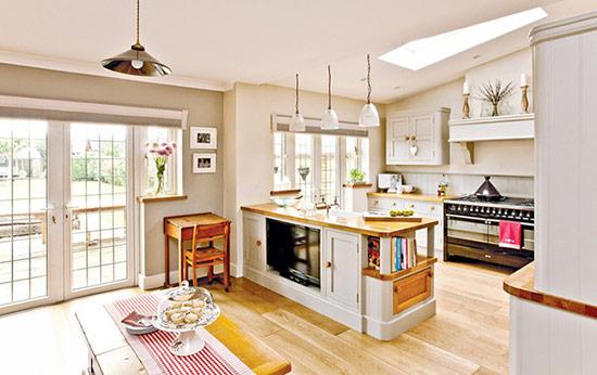 Phòng bếp và phòng ăn kiểu mở theo phong cách đồng quê với một chiếc khăn chải bàn kẻ sọc chạy dài.