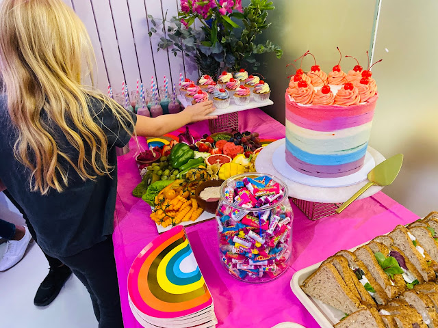 An 8 year old reaching for a cupcake on a buffet table with rainbow plates, lots of fruit, sweets and sandwiches