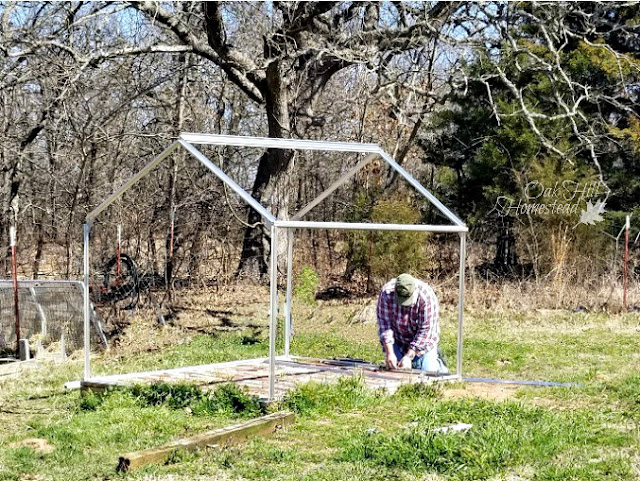 A man putting together the aluminum framed greenhouse.