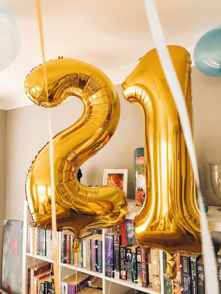 gold foil 21 balloons beside bookshelf with ribbons