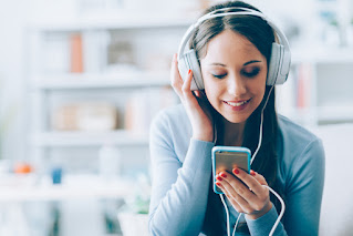 Brown hair caucasian woman with white headphones holding a mobile phone