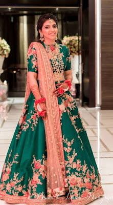 Emerald green sabyasachi lehenga with floral pattern blush pink.