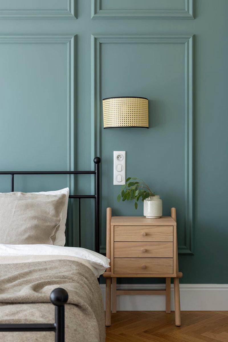 Dormitorio con pared enmarcada con molduras de escayola