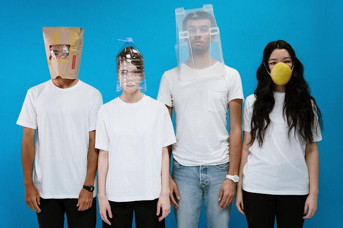 Quatro pessoas cobrindo o rosto de forma improvisada com saco, caixa, embalagem e casca de melão