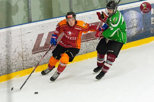 Hokejists ar roku atgrūžas no pretinieka, lai nepielaistu to pie ripas