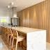 Cozinha com ilha em porcelanato e armário com churrasqueira em painel ripado de madeira!
