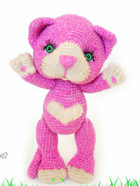 Pink amigurumi cat with green eyes and heart shaped belly