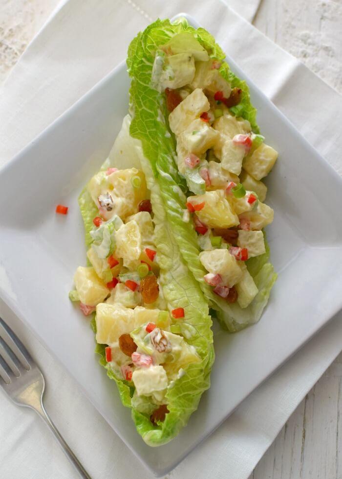 Ensalada de papas y manzana con célery, pimentón rojo, cebollines y pasas rubias, puede servirse en hojas de lechuga romana