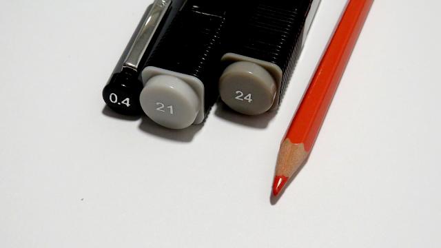 Rotulador calibrado del 0.4, rotulador a base de alcohol de la marca Tiger en la numeración 21 y 24 y un lápiz rojo