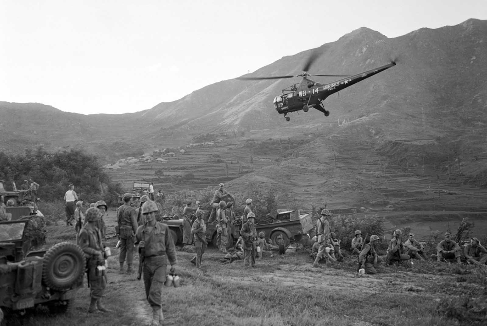 Helicopters were used on the battlefront as liaison planes and for evacuating the wounded. Here, one of the helicopters takes off over the heads of First Marine Division troops in a forward position on a mountain slope.