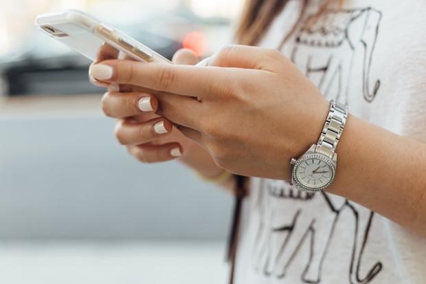 Mão feminina segurando um celular Iphone nas mãos