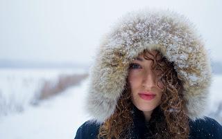 Garota cacheada com capuz de pele na neve, a neve nos cabelos lembra caspa