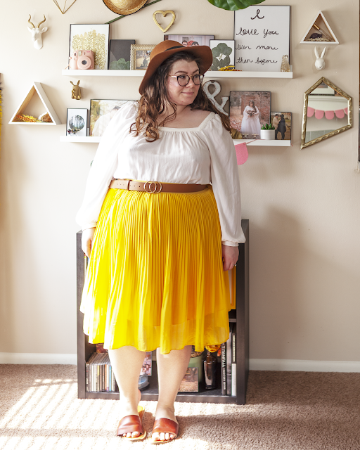 An outfit consisting of a camel brown panama hat, a long poet sleeve white square neck blouse tucked into a yellow pleated midi skirt and brown slide sandals.