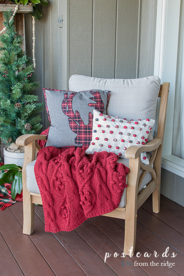 outdoor teak chair with red cable knit throw blanket and holiday pillows